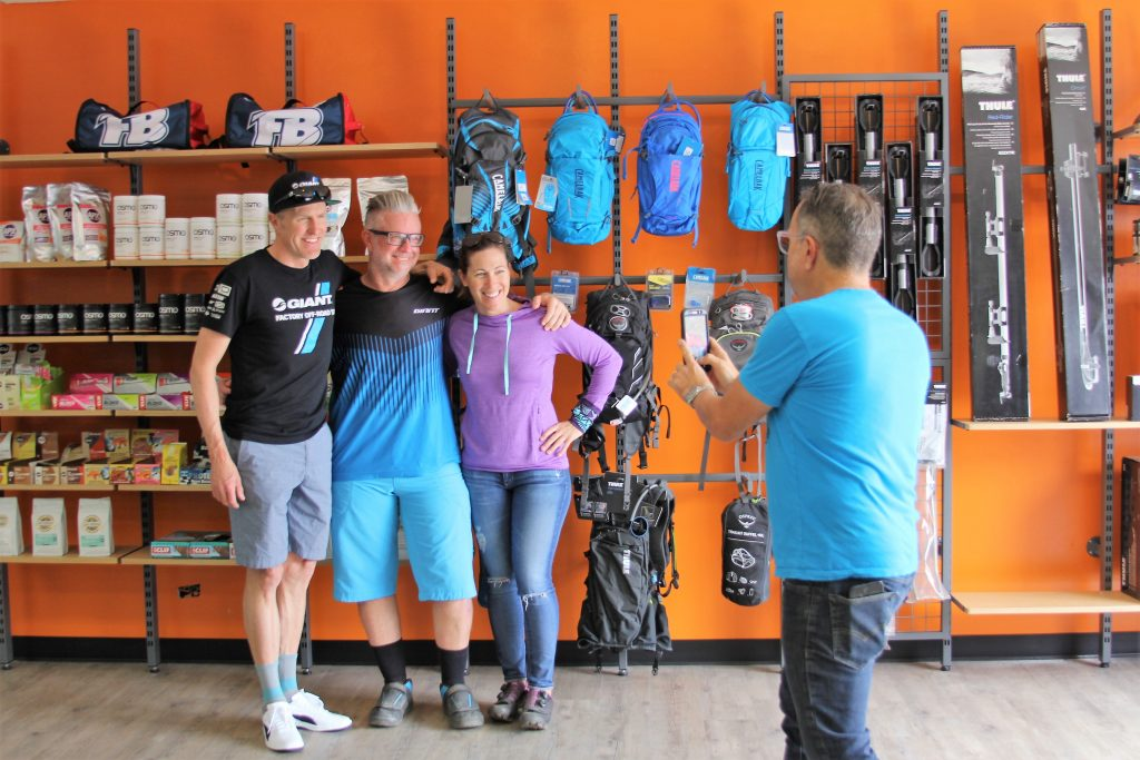 GIANT TEAM OFF-ROAD MEMBER CARL DECKER AND LIV AMBASSADOR LEIGH DONOVAN POSE FOR A PIC WITH A CUSTOMER.
