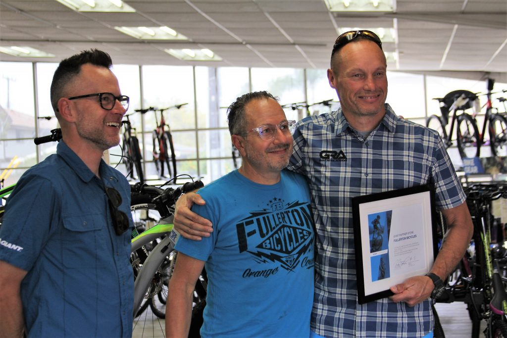 GIANT GENERAL MANAGER JOHN THOMPSON (R) AND GIANT REGIONAL MANAGER ERIC WOODS (L) PRESENTING MIKE FRANZE WITH A PLAQUE CERTIFYING FULLERTON BICYCLE AS THE NEWEST GIANT RETAIL PARTNER.