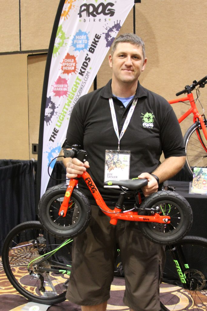 ITS NEVER TO EARLY TO START YOU TODDLER OUT ON BIKES. JEFF GIESLER FROM FROG BIKES HOLDING THEIR SMALLEST BIKE FOR YOUR FUTURE MTB CHAMP.